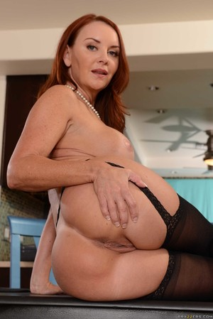 Redheaded lady Janet Mason shows off her sexy ass in black nylons