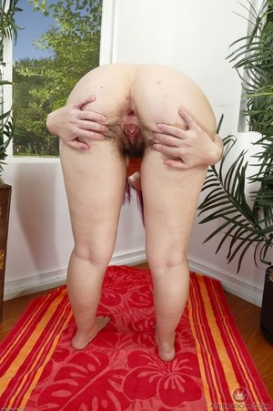 Hirsute female KoKo Kitty tugs on pubic hairs to spread her hairy bush
