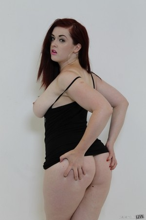 Curvaceous redhead works free of her black dress in pink argyle socks