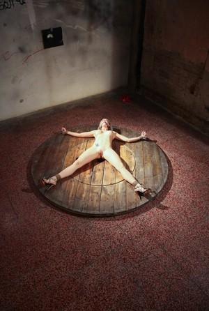 Naked Victoria lays like a starfish being tied to the round wooden scene