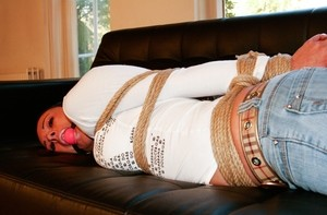 Bound with ropes and gagged brunette Vixen lays on the black sofa