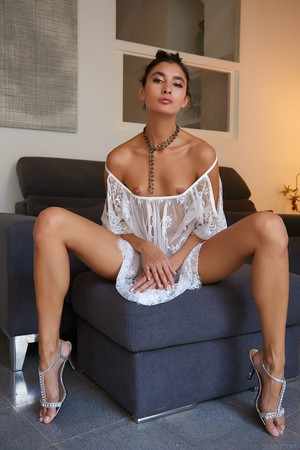 Luscious woman Bambi Joli with insidious face and long legs strips and poses