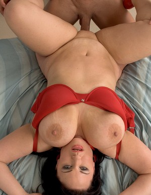 Overweight female with black hair catches a cumshot on her large breasts