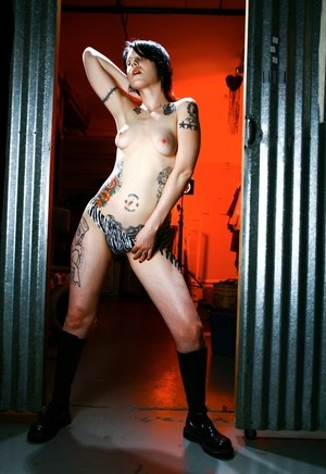 Alluring beauty wit dark hair and tattoos reveals her bald twat in Doc Martens