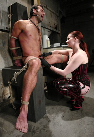 Redhead lady Claire Adams puts a man in a mouth spreader before torturing him