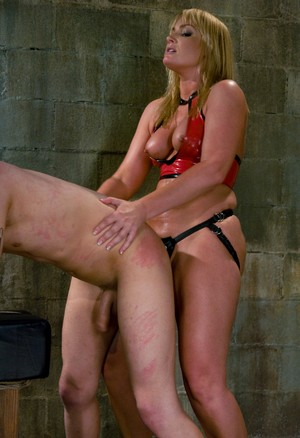 Flower Tucci in latex top uses strapon in pegging scene with Dean Strong