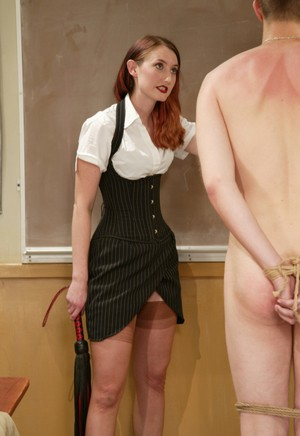 Redhead teacher makes a student write on board in the nude while flogging him