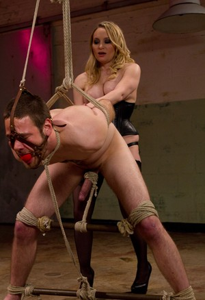 Rope bound and ball gagged man is affixed to spreaders before being pegged