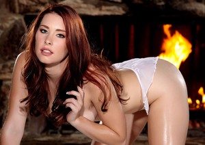 Hot redhead Melody Jordan slips off white teddy and panties in front of a fire