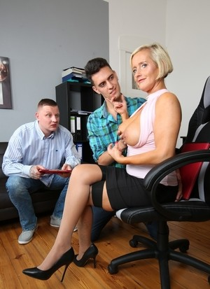 Mature German lady pleasures a couple of young boys in her office