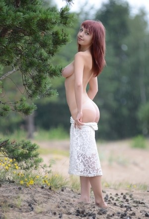 Hot redhead Ylika displays her lovely breasts during nude poses in woods
