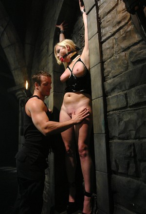 Hot Adrianna Nicole in latex & gag shackled to dungeon wall for BDSM playtime