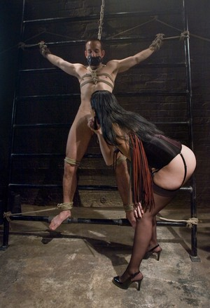 Brutal dominatrix January Seraph whips her male sub and bites his caged cock