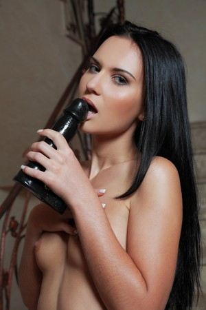Naked erotic Sinia A toying with her black dildo in high heels on the stairs