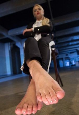 Four fully clothed dominatrix present their sexy feet for closeup inspection