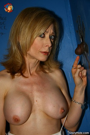 Mature pornstar Nina Hartley with big titties sucks BBC through gloryhole