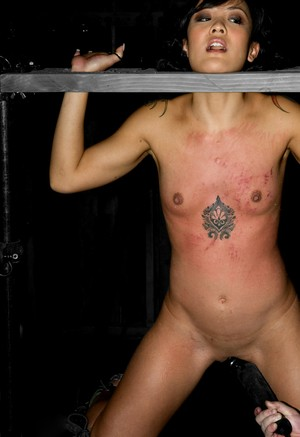 Pretty Asian sub has her hard nipples covered in hot wax while in the stocks