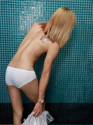 Horny blonde shemale stroking her cock and showing body in solo scene